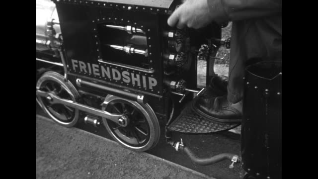 vídeos de stock e filmes b-roll de ms engineer on miniature train with us and french flags releases steam from engine the train is a gift from the children of wichita ks to sister city... - wichita