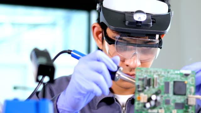vídeos y material grabado en eventos de stock de ingeniero o técnico de reparación de circuitos electrónicos con soldador - electrician