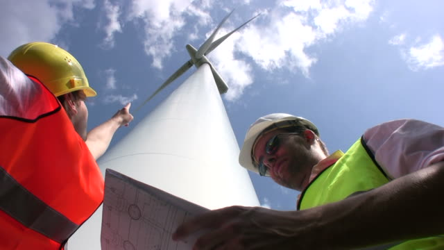 Engineer pointing at wind turbine