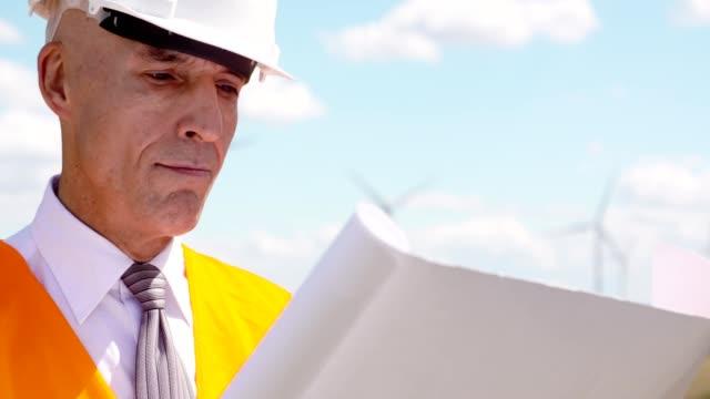 Engineer reading plan against Wind Turbine Farm