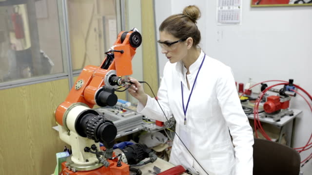 ingenieur reparatur roboterarm, panning shot - maschinenbau stock-videos und b-roll-filmmaterial