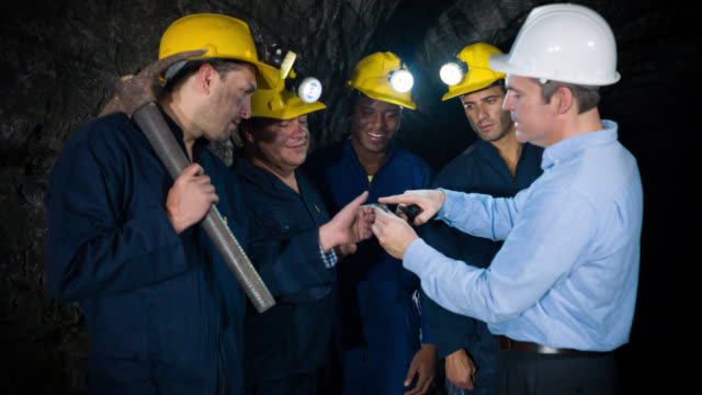 vídeos de stock e filmes b-roll de engineer showing miners what to look for - mineiro trabalhador manual