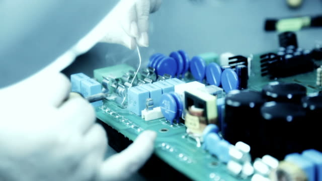 Engineer soldering circuit board with capacitor