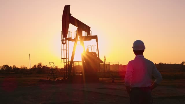 DS Engineer standing by the oil well at sunset