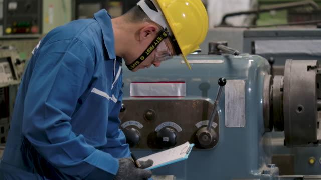 ingenieur, der in der fabrik steht und die werte überprüft - klemmbrett stock-videos und b-roll-filmmaterial
