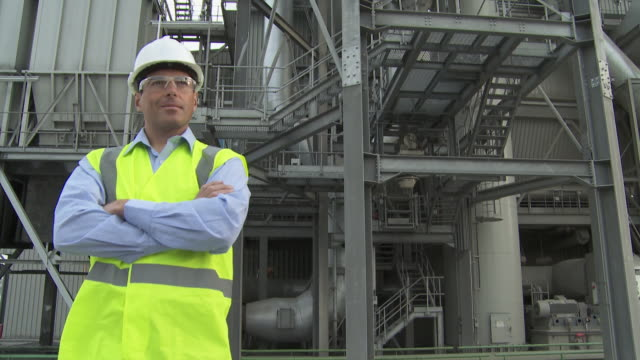 engineer standing outside factory, tilt down - helm stock-videos und b-roll-filmmaterial