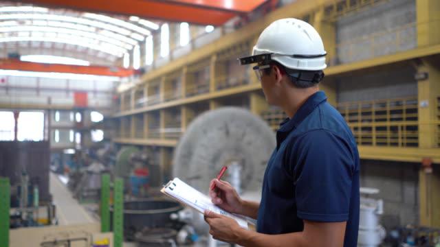クリップボードを見ながら冶金工場の運用を監督するエンジニア - クリップボード点の映像素材/bロール