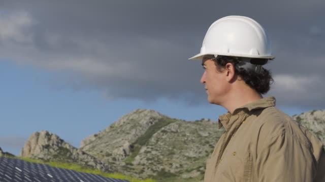 cu engineer surveying mountainous area with photovoltaic (solar) plant / malaga, spain - 30代の男性一人点の映像素材/bロール