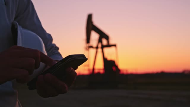 DS Engineer talking on a mobile phone while checking the oil well at sunset