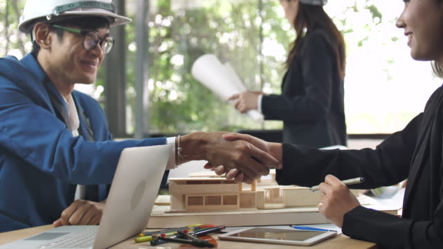 engineer talking with his client and shake hands over architectural model - dealing cards stock videos and b-roll footage