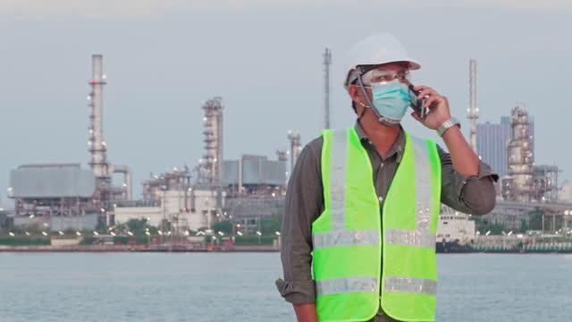 vidéos et rushes de ingénieur parlant avec le smartphone à l'industrie de raffinerie de pétrole pour l'énergie ou l'arrière-plan de construction. - docker