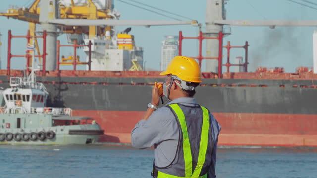 ビジネスロジスティクス輸入輸出輸送または貨物輸送のためのターミナル商業港でwalkie-talkieと話すエンジニア。 - 造船所点の映像素材/bロール