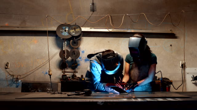 Engineer teaching apprentice to use welding machine