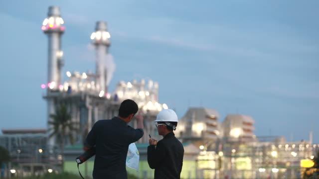 vídeos de stock e filmes b-roll de engineer team working at power plant with plane - central elétrica
