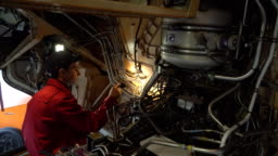 Engineer technician inspects the inside of the aircraft with a flashlight.