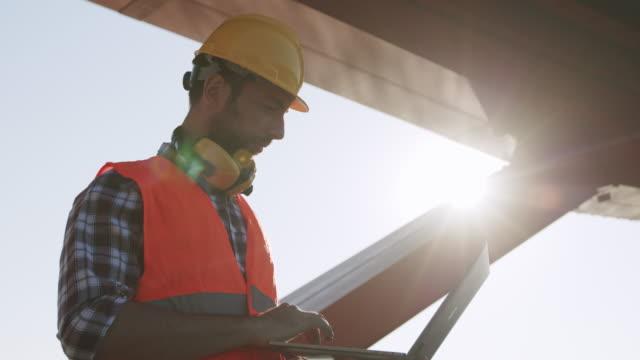 vídeos y material grabado en eventos de stock de ingeniero utilizar computadora portátil en el sitio de construcción al amanecer - material de construcción