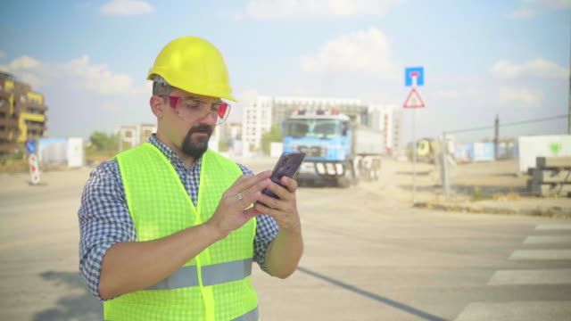 engineer use smart phone on construction site - technician stock videos & royalty-free footage