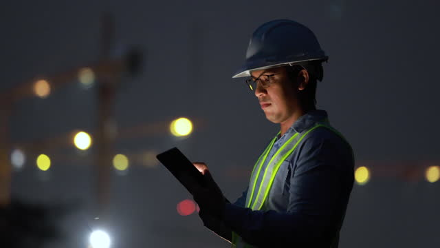 engineer use tablet at construction site at night time - foreman stock videos & royalty-free footage