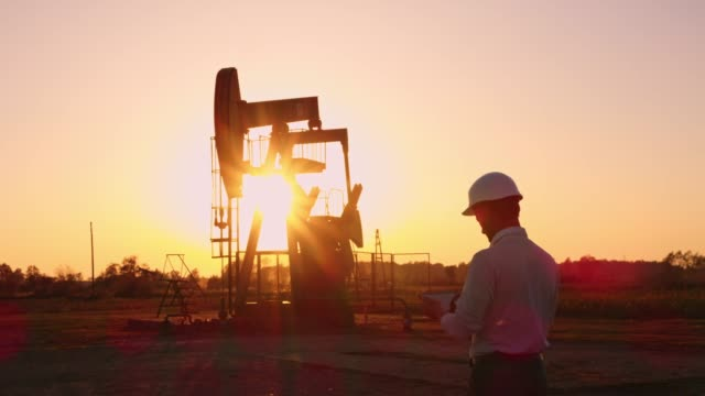 vídeos de stock e filmes b-roll de ds engineer using a digital tablet while checking the oil well at sunset - gasolina