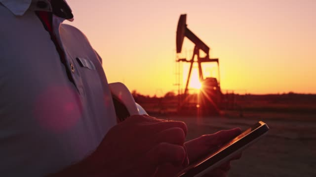 ds r/f engineer using a tablet for checking the oil well functions - industria petrolifera video stock e b–roll