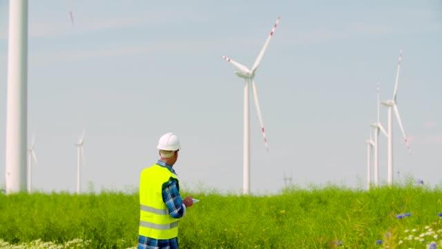 Engineer using digital tablet while Wind Turbine Inspection at windmill farm