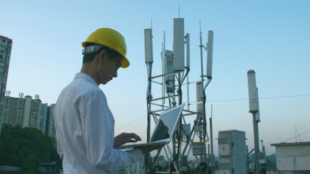 engineer using laptop check 5g telecommunications base station tower - tower stock videos & royalty-free footage