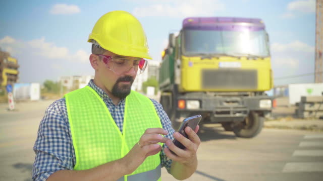 engineer using mobile phone on construction site - dump truck stock videos & royalty-free footage