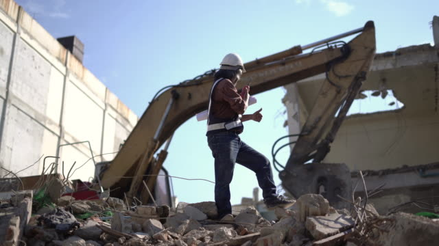 engineer using walkie-talkie for command at construction site. - bulldozer stock videos and b-roll footage