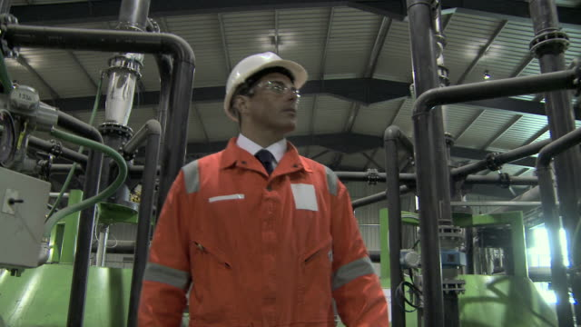 Engineer walking through factory and inspecting machinery