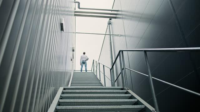 ingegnere slo mo che sale le scale della passerella in acciaio della fabbrica - low angle view video stock e b–roll