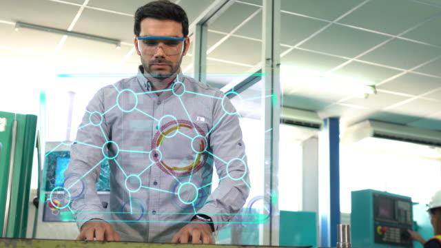 engineer wearing safety glass works on a computer , screens show animated glow holographic hud rotating . modern high-tech industry 4.0 electronics production factory. - gui点の映像素材/bロール