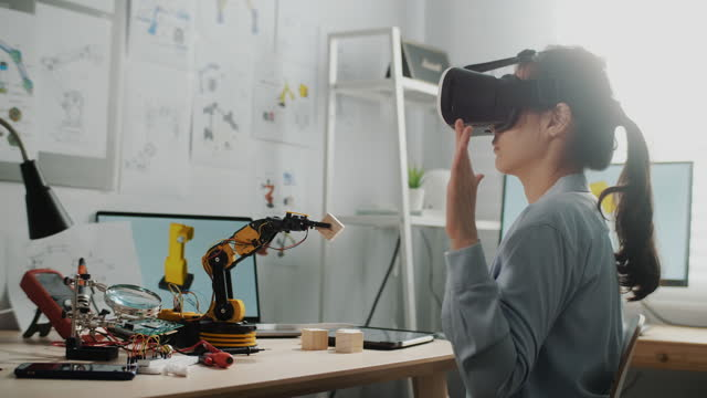 engineer wearing virtual reality headset and gesturing while while sitting at her desk in desk and working - cyberspace stock videos & royalty-free footage