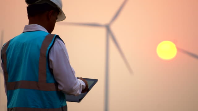 engineer with digital tablet in front of wind turbines at sunset - power line stock videos & royalty-free footage