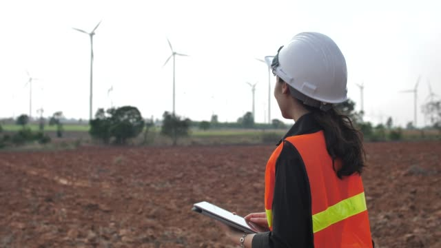 Engineer with digital tablet in front of wind turbines