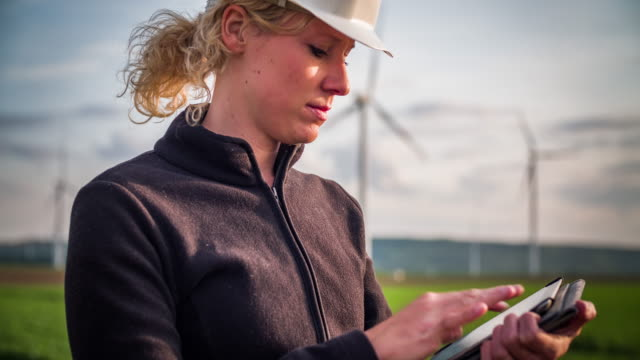 Engineer with digital tablet inspecting Wind Turbines - Women in STEM