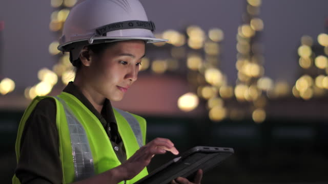 engineer with tablet at industrial, oil or gas plant - industria petrolifera video stock e b–roll