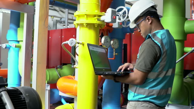 Engineer with tablet at industrial, oil or gas plant