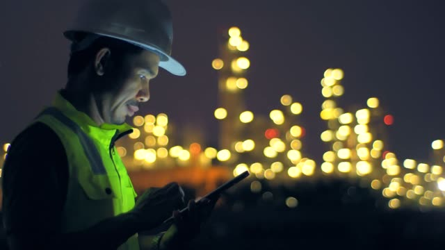 engineer with tablet at industrial oil or gas refinery background - inspector stock videos & royalty-free footage