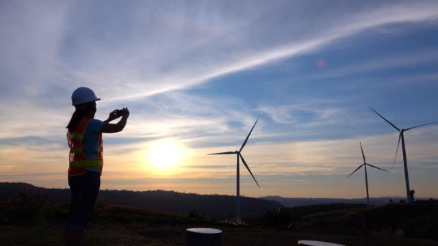 ingenieurfrauen in windkraftanlagen bei sonnenuntergang. - gegenlicht stock-videos und b-roll-filmmaterial