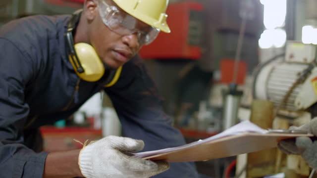 vídeos y material grabado en eventos de stock de trabajador de ingeniero que obtiene la comprobación en el portapapeles de papel - tablilla con sujetapapeles