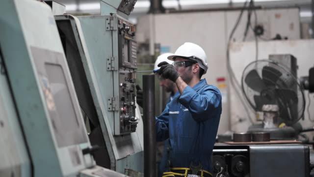 ingenieurarbeiter, der mit produktionsmaschine im werk arbeitet - manufacturing occupation stock-videos und b-roll-filmmaterial