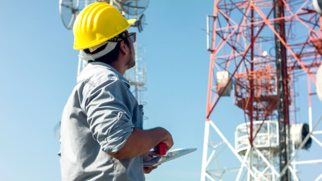 hd dolly : engineer working at telecommunication tower site. - telecommunications equipment stock videos and b-roll footage