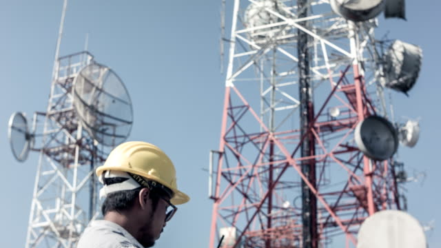 hd dolly : engineer working at telecommunication tower site - telecommunications equipment stock videos and b-roll footage