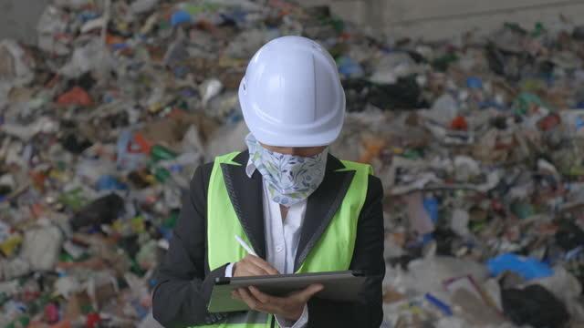 covid-19パンデミックのリサイクルセンターで働くエンジニア。廃棄物分離工場で作業している間、保護フェイスマスクを着用したメンテナンスエンジニア。 - 廃棄物処理点の映像素材/bロール