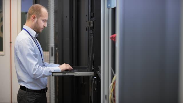 ds it エンジニアは、コンピューター室のラップトップに取り組んで - エンジニア点の映像素材/bロール