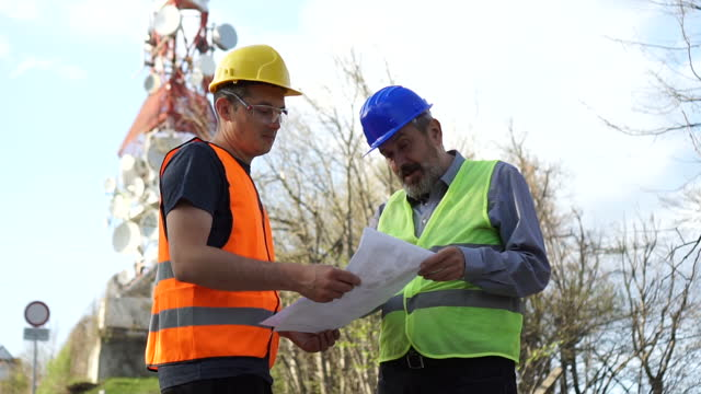 engineer working on the field near a telecommunications tower - super slow motion stock videos & royalty-free footage