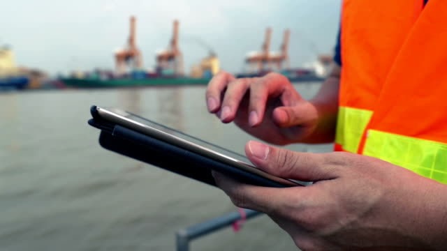 Engineer working using digital tablet with as a Cargo port background