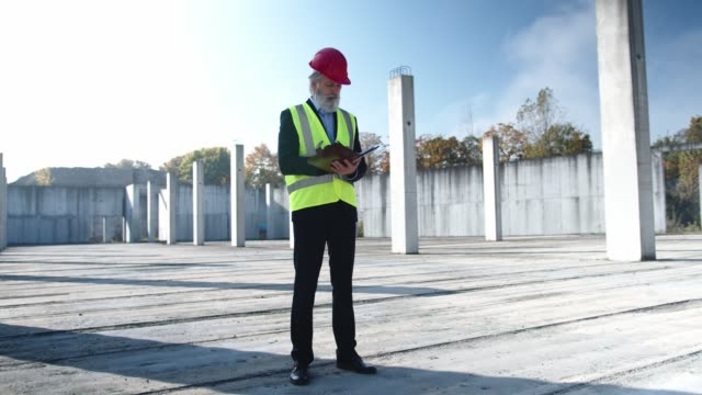 engineer writing notes on the notepad, standing still on empty construction site - health and safety stock videos & royalty-free footage