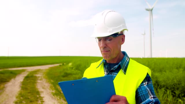 Engineer Writing On Clipboard While Doing Wind Turbine Inspection