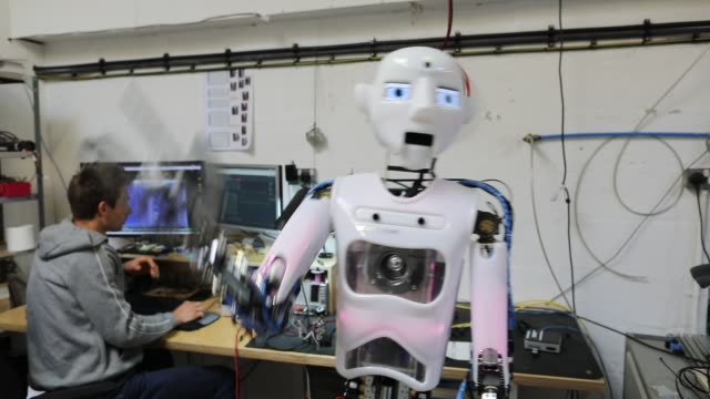 Engineered Arts electrical engineer Beni Szlivka checks a RoboThespian robot that is being built at the company's headquarters in Penryn on May 9...